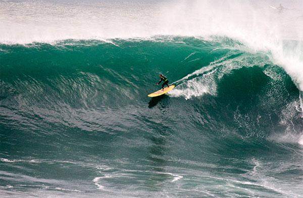 Chris Bertish surfant une vague en stand up paddle en Afrique du Sud